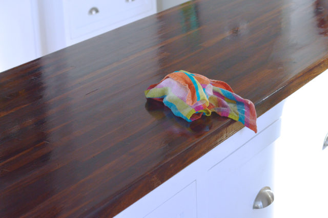 Apply pure tung oil to your sanded and cleaned butcher block island - it's non toxic and a food safe finish.