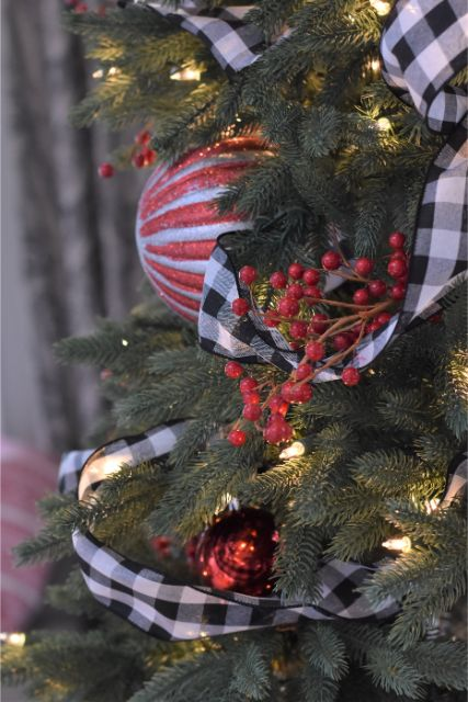 Details of berries, buffalo check ribbon and ornaments on this modern, family-friendly Christmas tree.