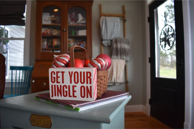 Get your jingle on sign with festive red ornaments